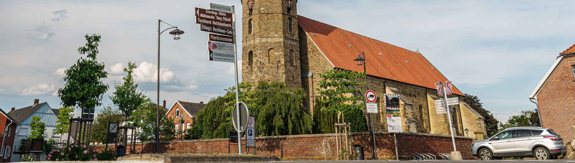Blick auf die Kirche Badbergen mit Wegweiser zu den Sehenswürdigkeiten der Gemeinde