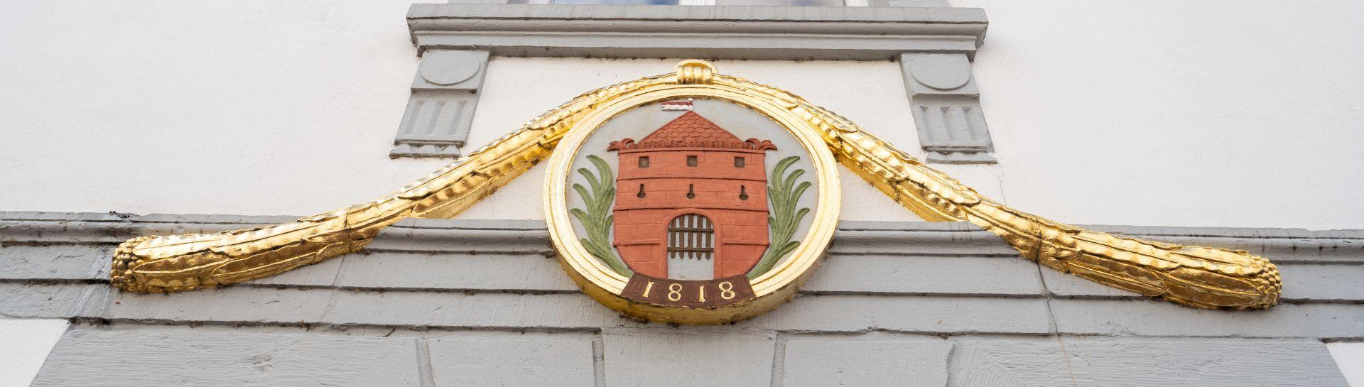 Blick auf das Wappen am Rathaus in Quakenbrueck über dem Eingang zum Buergerbuero